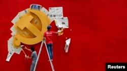 Para pekerja mengecat ulang bendera Partai Komunis China di Museum Revolusi Nanhu di Jiaxing, Provinsi Zhejiang, 21 Mei 2020. (Foto: Reuters)