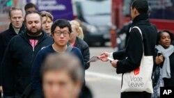 """Seorang pendukung keluarnya Inggris dari Uni Eropa (""""Brexit"""") membagikan leaflet permintaan dukungan terhadap Brexit di London (foto: dok)."""