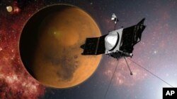 FILE - In this artist concept provided by NASA, the MAVEN spacecraft approaches Mars on a mission to study its upper atmosphere. NASA said Thursday that the satellite's route was tweaked to avoid a collision with one of the planet's two small moons.