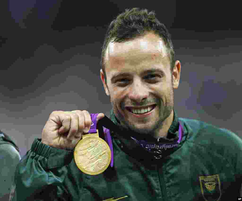 Oscar Pistorius celebrates with his gold medal after winning the men's 400m T44 classification during the London 2012 Paralympic Games, Sept. 8, 2012.