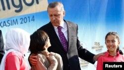 Turkish President Recep Tayyip Erdogan talks with students of the Tevfik Ileri Imam Hatip School during its opening ceremony in Ankara, Nov. 18, 2014.