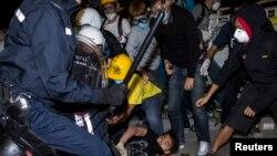 Seorang pemrotes terjatuh saat bentrok dungeon police anti huru-hara di luar guiding praline di Hong Kong (19/11).