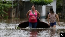 A woman (L) and her daughter carry a table on a flooded street as they leave their home in San Miguel neighborhood in Asuncion, Paraguay. Dec. 27, 2015.