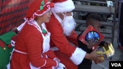 Santa and Mrs. Claus distributed gifts to the kids at the Corps' annual holiday party. (M. O'Sullivan/VOA)