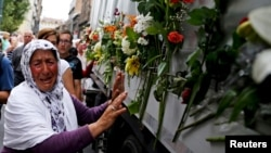 A woman cries beside a truck carrying 136 coffins of newly identified victims of the 1995 Srebrenica massacre, in front of the presidential building in Sarajevo July 9, 2015. The bodies will be on July 11, the anniversary of the massacre. (REUTERS/Dado Ruvic)