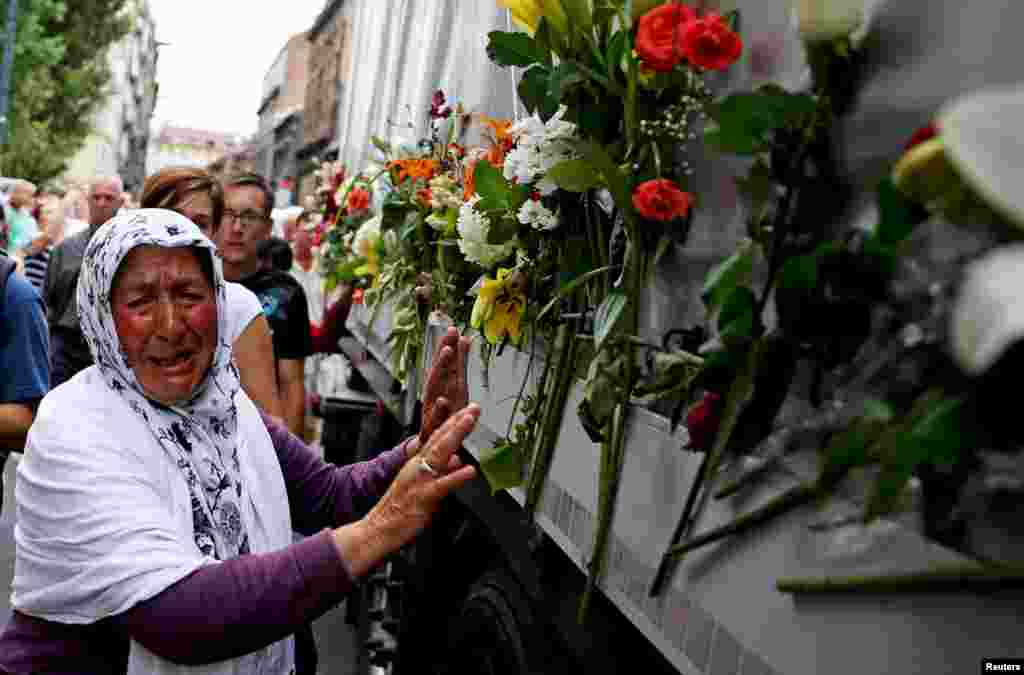 A woman cries beside a truck carrying 136 coffins of newly identified victims of the 1995 Srebrenica massacre, in front of the presidential building in Sarajevo. The recently identified victims will be transported to the memorial center in Potocari where they will be buried on July 11, the anniversary of the massacre when Bosnian Serb forces slaughtered 8,000 Muslim men and boys and buried them in mass graves in Europe's worst massacre since World War II.