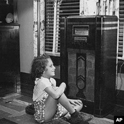 一个小女孩儿在听广播