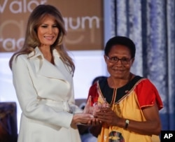 FILE - First lady Melania Trump presents the 2017 Secretary's of State's International Women of Courage (IWOC) Award to Veronica Simogun from Papua New Guinea, March 29, 2017, at the State Department in Washington.