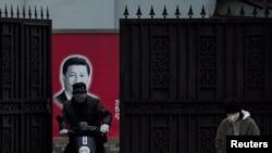 戴著口罩的行人從上海街頭一個有著習近平畫像的大門前經過(2020年2月10日)