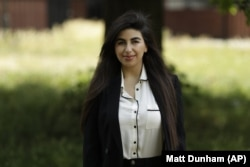 In this photo taken on Thursday, June 11, 2020, recent university graduate Sahar Shabani poses for a photograph in London. Shabani, 22, did a three-month remote internship with a development charity based in Thailand from her parents' home in South London
