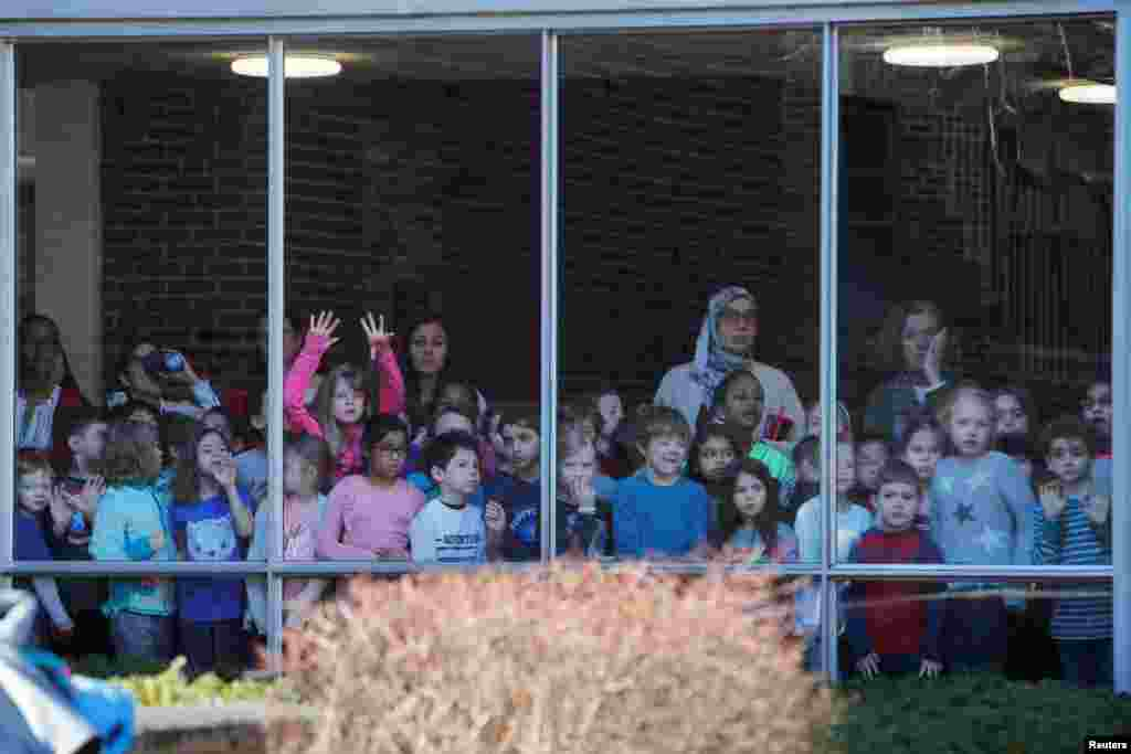 Students watch from a window as Democratic 2020 U.S. presidential candidate and U.S. Senator Elizabeth Warren arrives to vote on Super Tuesday in Cambridge, Massachusetts.