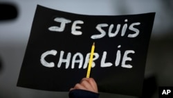 """A Lebanese journalist holds up her pen and a French placard that reads, """"I am Charlie."""" The killings in Paris at the satiric newspaper Charlie Hebdo has re-ignited debate about blasphemy. (AP Photo/Hussein Malla)"""