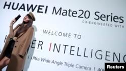 一名模特站在华为在英国伦敦发起的华为Mate20系列的广告牌前。(2018年10月16日)
