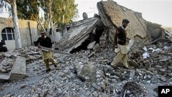 Pakistani soldiers walk through the rubble of a damaged building at the site of suicide bombing in Ghalanai, the main town in Pakistani tribal area Mohmand, Dec. 6, 2010