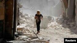 지난 17일 시리아 알레포에서 한 소녀가 정부군 포격을 피해 달아나고 있다. 반정부 단체가 제공한 사진이다. (자료사진)