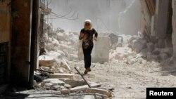 Seorang anak perempuan berlari menghindari serangan dari pasukan Suriah di Aleppo (17/5).