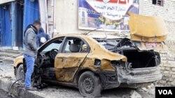 Seorang warga di Baghdad memeriksa mobilnya yang hancur akibat ledakan bom di Baghdad (23/2).