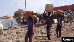 FILE - Men carry humanitarian aid in Mopti, Mali, February 4, 2013.