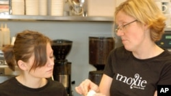 At Moxie Bakery and Cafe, Christina Quinn (L) gets advice from Elin Ross on more than how to bake cupcakes