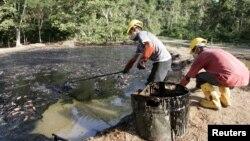 Trabajadores ecuatorianos limpian un pozo contaminado de petróleo en la zona de Taracoa, en el Amazonas.