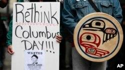 """2011-й рік. Демонстрант тримає плакат із закликом """"Переосмисліть День Колумба"""""""