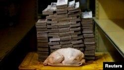تصویر مربوط به اوت ۲۰۱۸ که یک مرغ ۲.۴ کیلوگرمی را در کنار پول مورد نیاز (پول ملی ونزوئلا) برای خرید آن نشان می دهد.