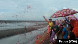 Warga tabur bunga ke makam keluarga yang sudah tenggelam oleh lumpur Lapindo, 30 Mei 2016 (Foto: VOA/Petrus)