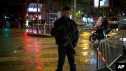 A French police officer stands guard near the Bataclan concert hall in Paris, Saturday, Nov. 12, 2016. The hall was among venues targeted a year ago by terrorists in coordinated attacks that left 130 people dead.
