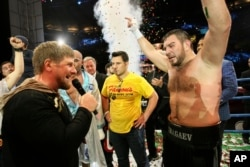 "Chechen leader Ramzan Kadyrov, left, congratulates Uzbekistan's ""White Tyson"" Ruslan Chagaev, right, while celebrating his victory over American Fres Oquendo after their WBA heavyweight boxing championship fight at Ahmat Arena, in Grozny, Russia."