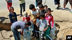 FILE - Syrian refugees fill up water bottles at a temporary refugee camp in the eastern Lebanese town of Faour near the border with Syria, August 28, 2013.