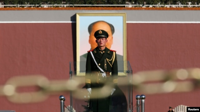 FILE - A paramilitary soldier stands guard behind a chain as the giant portrait of the late Chinese Chairman Mao Zedong is seen in the background in Tiananmen square, Nov. 12, 2013.