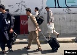 """Beberapa warga Afghanistan tampak di bandara internasional """"Hamid Karzai"""" di Kabul hari Minggu (15/8)."""