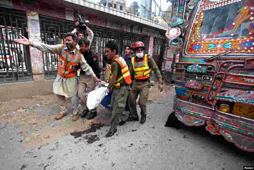 Rescue workers carry a dead body away from the site of a blast at University Road in Peshawar, Pakistan, April 29, 2013.