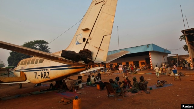 A family displaced by inter-communal violence in the country sit near  a plane in a camp for displaced persons at Bangui M'Poko International Airport February 20, 2014