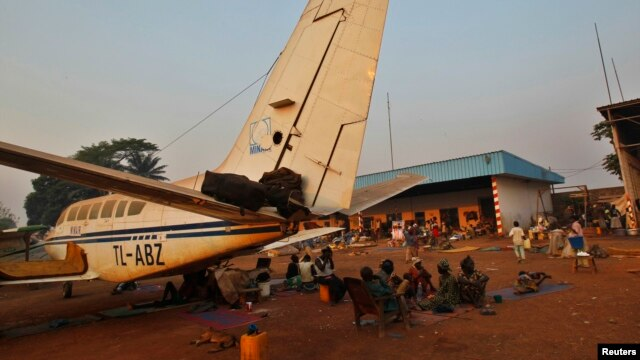 A family displaced by inter-communal violence in the country sit near  a plane in a camp for displaced persons at Bangui M'Poko International Airport, Feb. 20, 2014.
