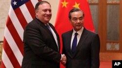 امریکی وزیر خارجہ پومپیو دورہ چین میں چینی وزیر خارجہ سے مصافحہ کر رہے ہیں