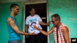 Danilo Maldonado (izq.) saluda a un amigo delante de la vivienda de la casa de su madre María Victoria Machado, en La Habana, en esta foto de octubre de 2015 (AP).