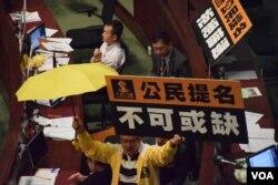 人民力量立法會議員被主席曾鈺成逐出會議廳時,高舉黃傘及標語。(美國之音湯惠芸)