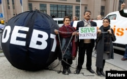"""FILE - Protesters asking to drop the Pakistan's debt stand a """"Friends of Democratic Pakistan"""" meeting in Brussels, Belgium."""