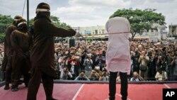 Polisi syariah melakukan hukuman cambuk terhadap seorang pria gay di luar masjid di Banda Aceh, provinsi Aceh, Selasa