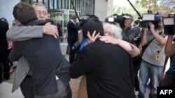 Couples embrace in front of the media outside the High Court of Australia, in Canberra, Dec. 12, 2013.
