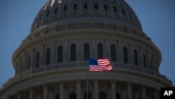 FILE - An American flag flies in front of the dome of the United States Capitol building, July 26, 2011.