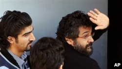 Police officers escort journalist Soner Yalcin, right, during a medical check in Istanbul, Turkey, Feburary 17, 2011