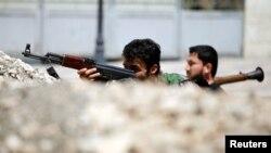 Các chiến binh thuộc Quân đội Syria Tự do ngồi sau rào phòng thủ trên một con đường ở Aleppo