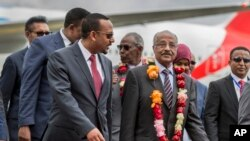 FILE - Eritrea's Foreign Minister Osman Sale, center-right, is welcomed by Ethiopia's Prime Minister Abiy Ahmed, center-left, upon the Eritrean delegation's arrival at the airport in Addis Ababa, Ethiopia, June 26, 2018.