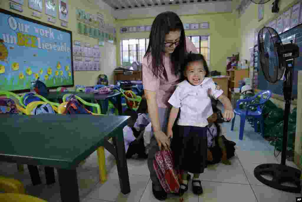 A Filipino teacher tries to prevent a crying student from getting out of the classroom during the first day of school at the President Corazon C. Aquino Elementary School in Manila, Philippines.