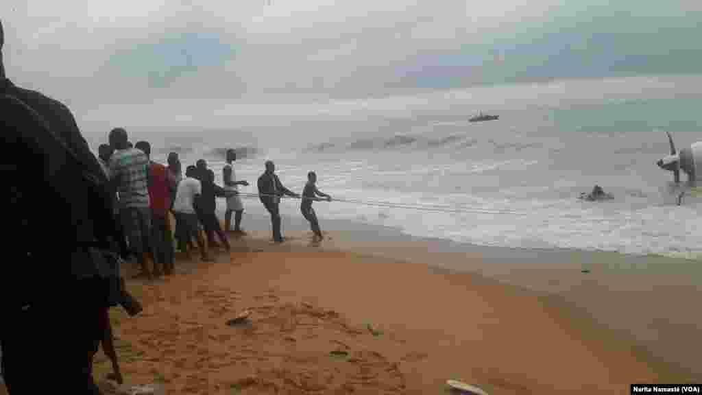Des riverains aident à tirer l'épave d'avion abîmée au bord de la mer au Port Bouet, au large d'Abidjan, Côte d'ivoire, 14 octobre 2017. (VOA/Narita Namasté)