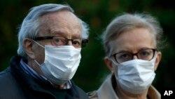 Penzioneri sa zaštitnim maskama u dozvoljenoj šetnji tokom trajanja zabrane kretanja za ostale kategorije stanovništva, u sklopu borbe protiv širenja zaraze koronavirusom, u Beogradu, Srbija, 24. aprila 2020. (AP Photo/Darko Vojinović)