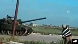 A man throws a rock at a passing tank in a location given as Deraa on April 25, 2011, in this still image from an amateur video