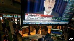 The news conference of Federal Reserve Chairman Ben Bernanke appears on a television screen at a trading post on the floor of the New York Stock Exchange, Dec. 18, 2013.